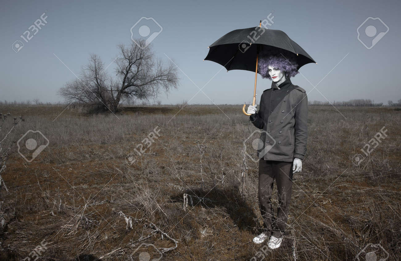 Sad alone clown outdoors holding umbrella and waiting for the rain. Artistic darkness and colors added Stock Photo - 7376500