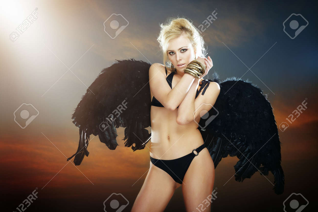 Woman in the lingerie with black angel wings against the hell sky background. Artistic grain and colors added. Natural light and darkness Stock Photo - 7872484