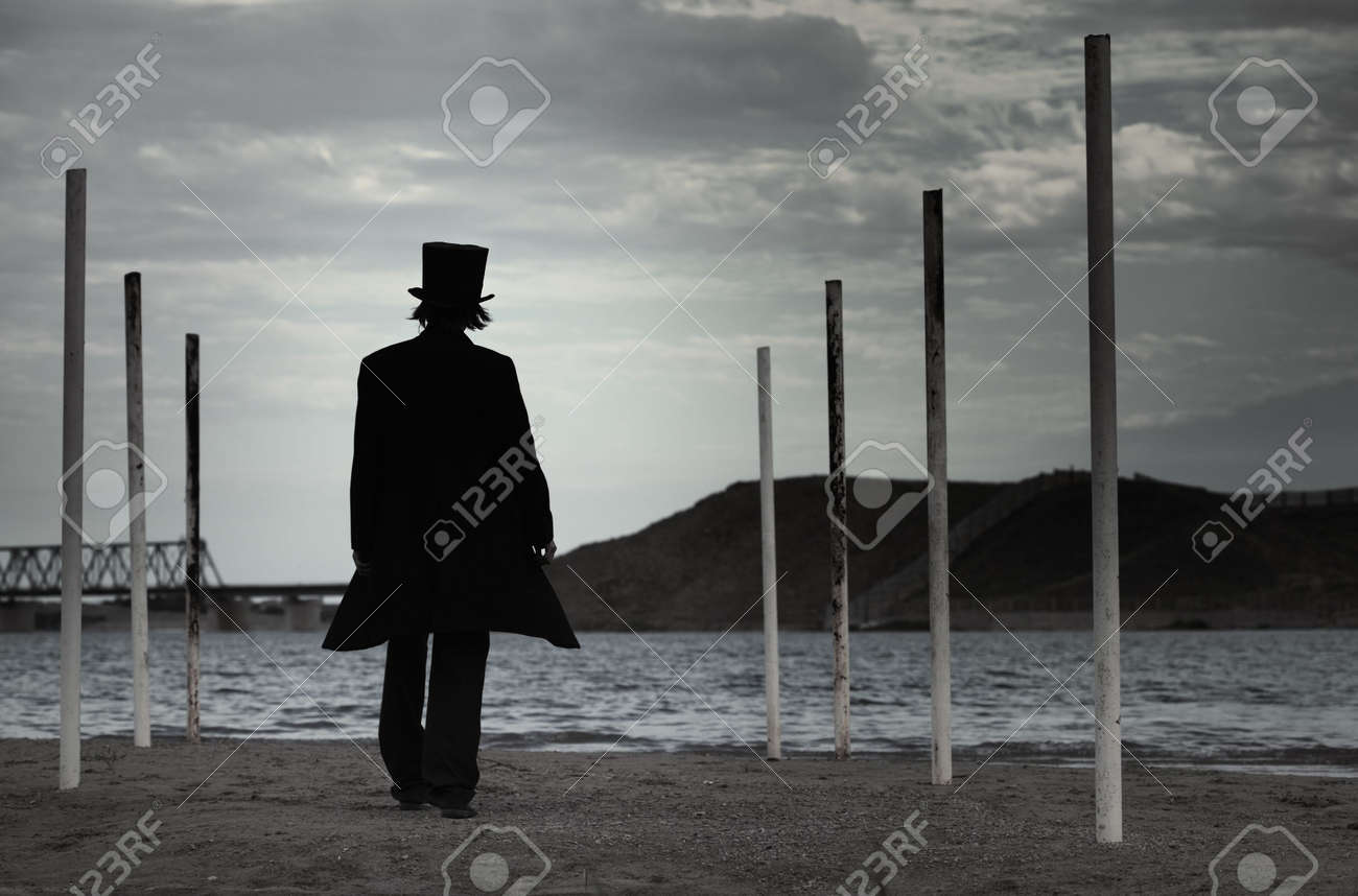 Rear view on alone man in the black coat and top-hat going to the sea. Natural darkness. Artistic colors added - 8016272