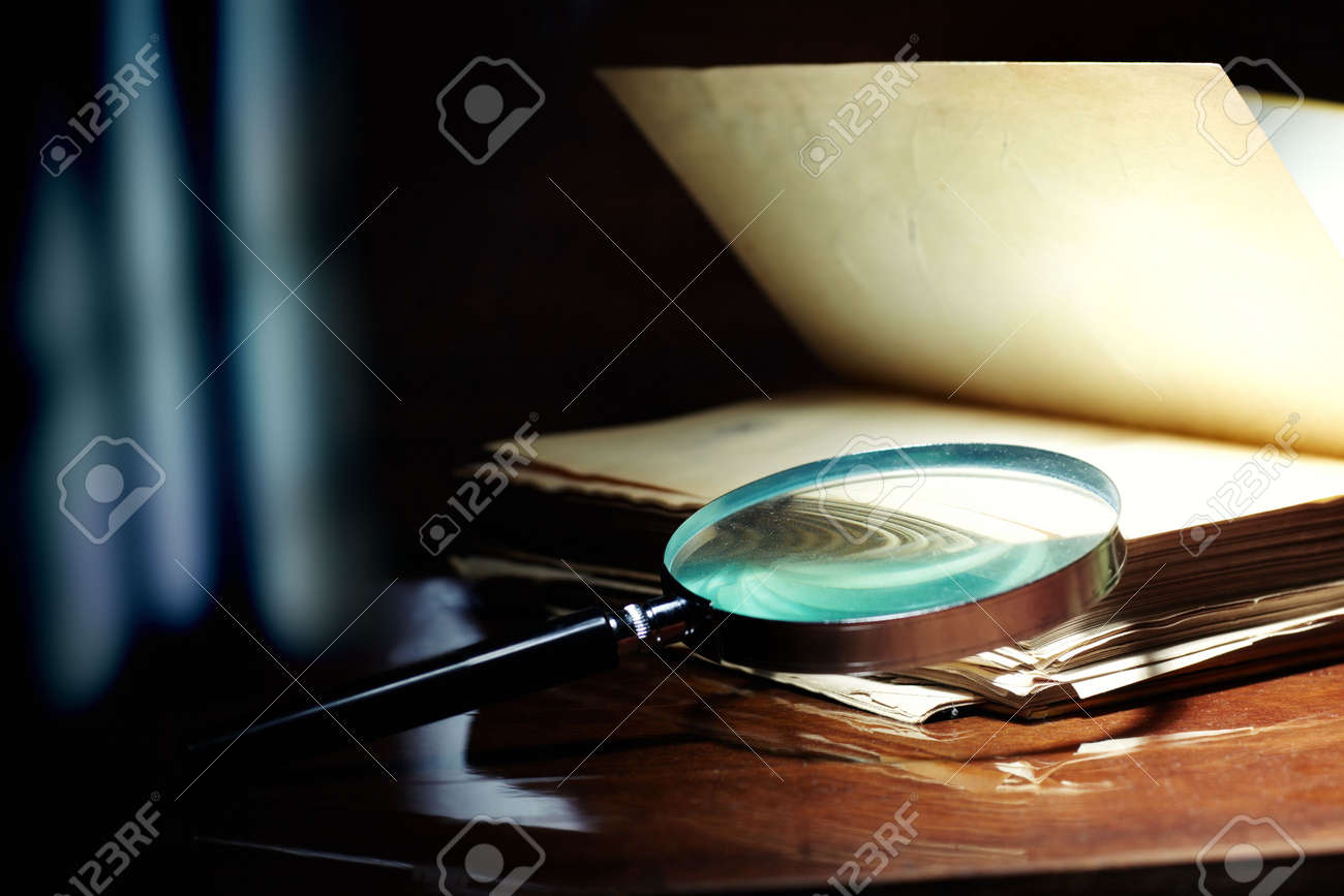 Old book and magnifier glass on a dark background as a symbol of knowledge and science - 8233909
