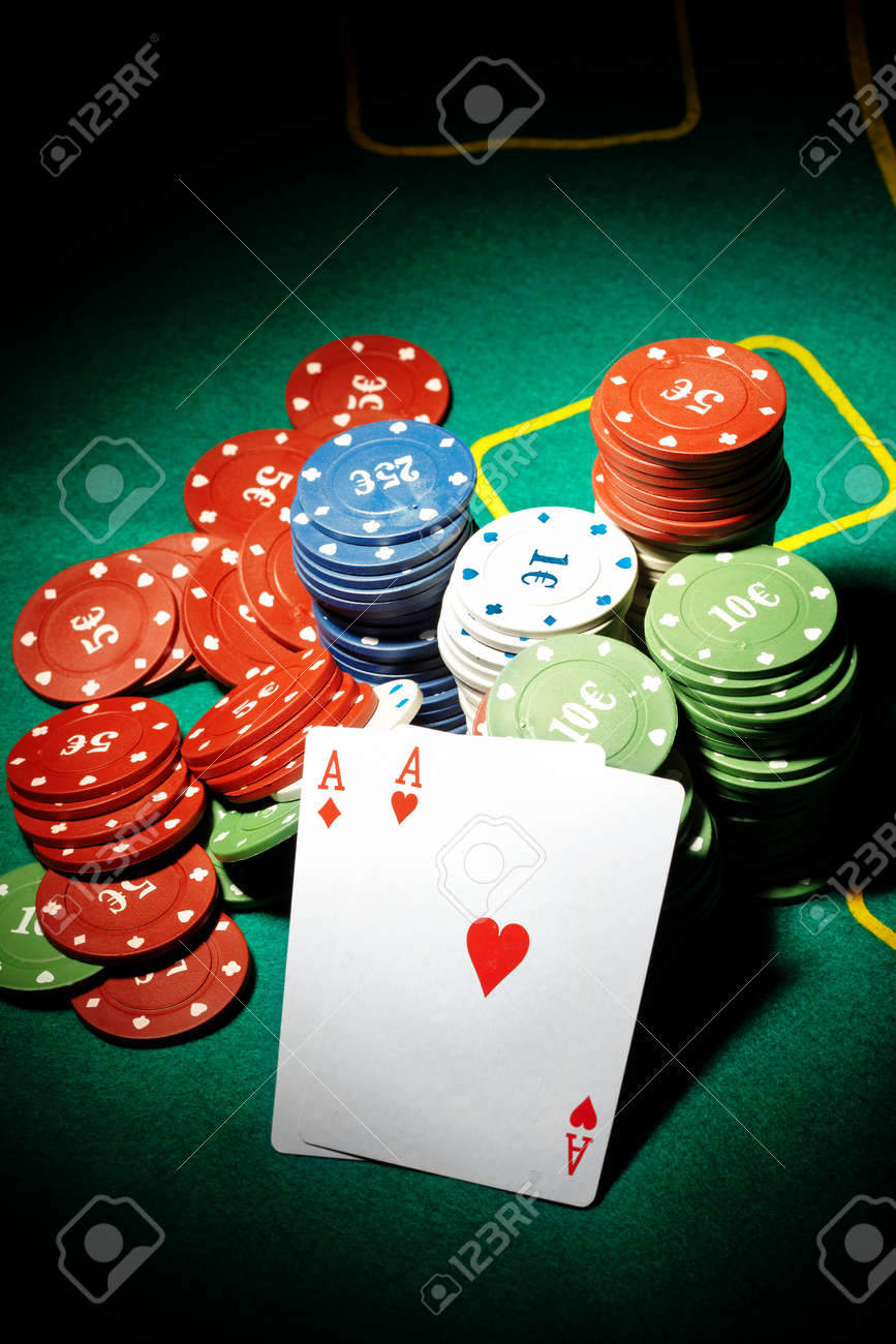 Pair of aces and poker chips on a green table in casino - 8812079