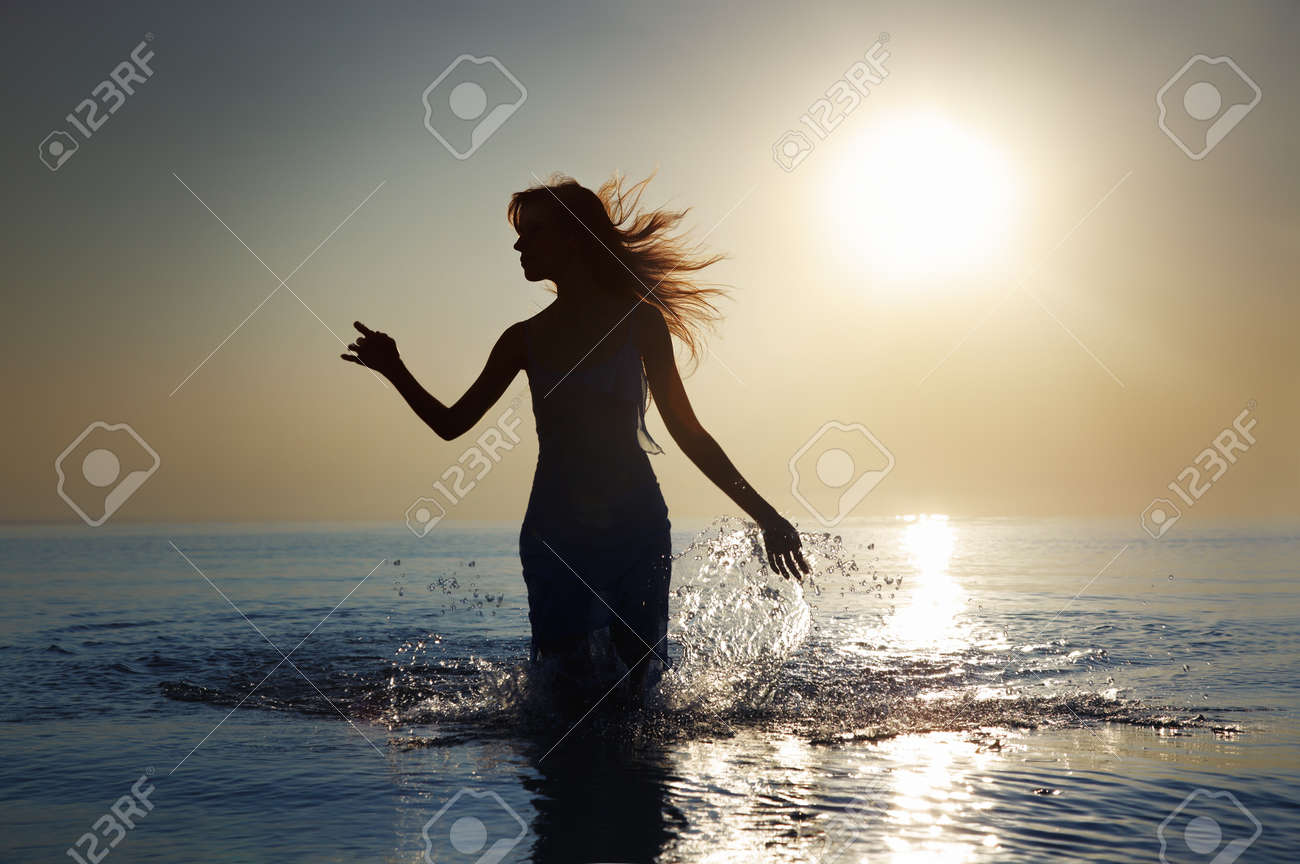 Silhouette of the woman with long hairs walking in the water during sunrise. Natural darkness and colors - 8908445