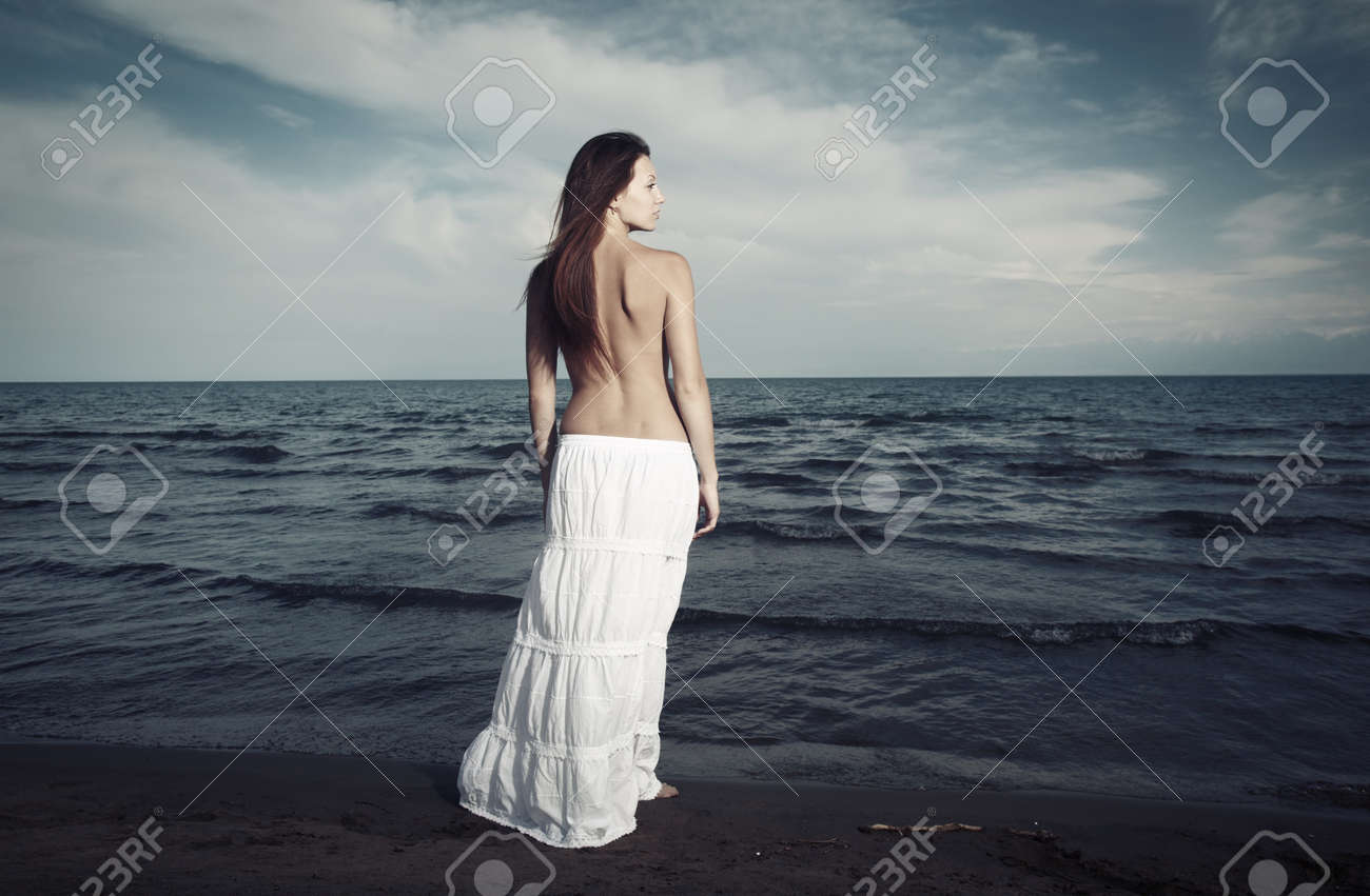 Single lady with naked back standing at the cold sea. Artistic colors added Stock Photo - 9278431