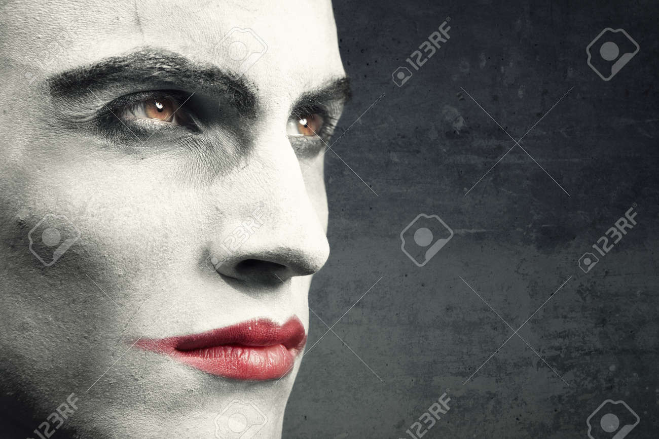 Man with vampire makeup on a dark grungy background. Natural makeup and background. Text can be added onto the empty space - 9278456
