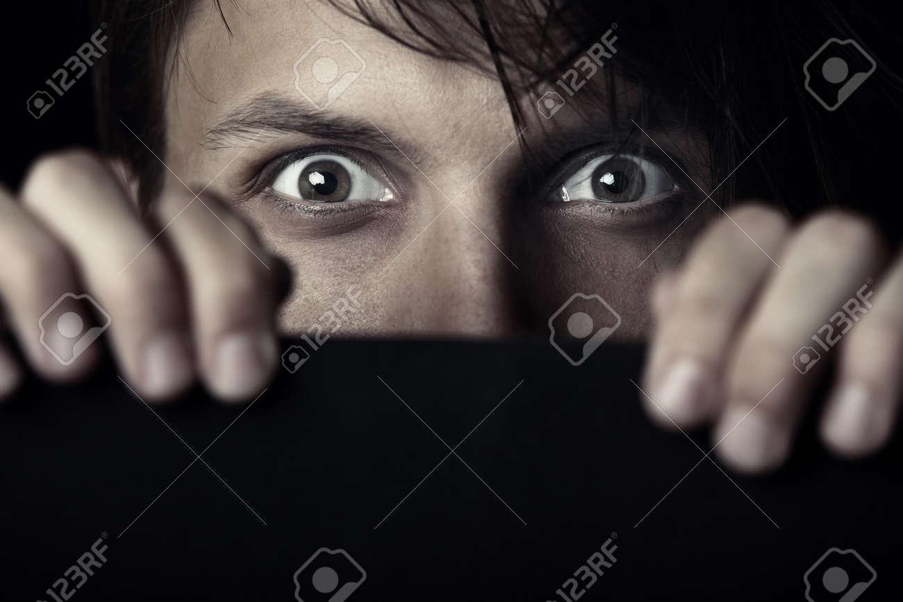 Afraid human hiding behind the dark board - 10719199