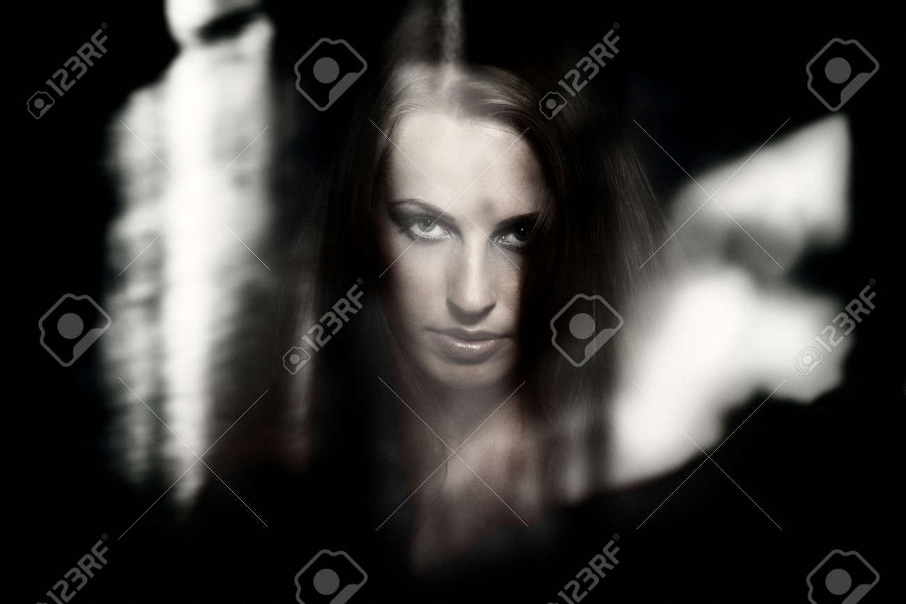 Female witch behind the dark glass with reflections Stock Photo - 11032586