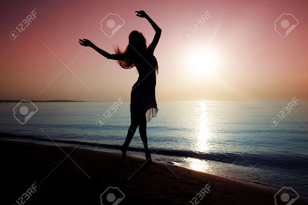 Silhouette of elegant lady dancing at the beach during sunset Stock Photo - 13742424