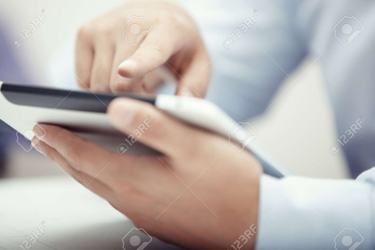 Hands of businessman using tablet PC at office - 14276862