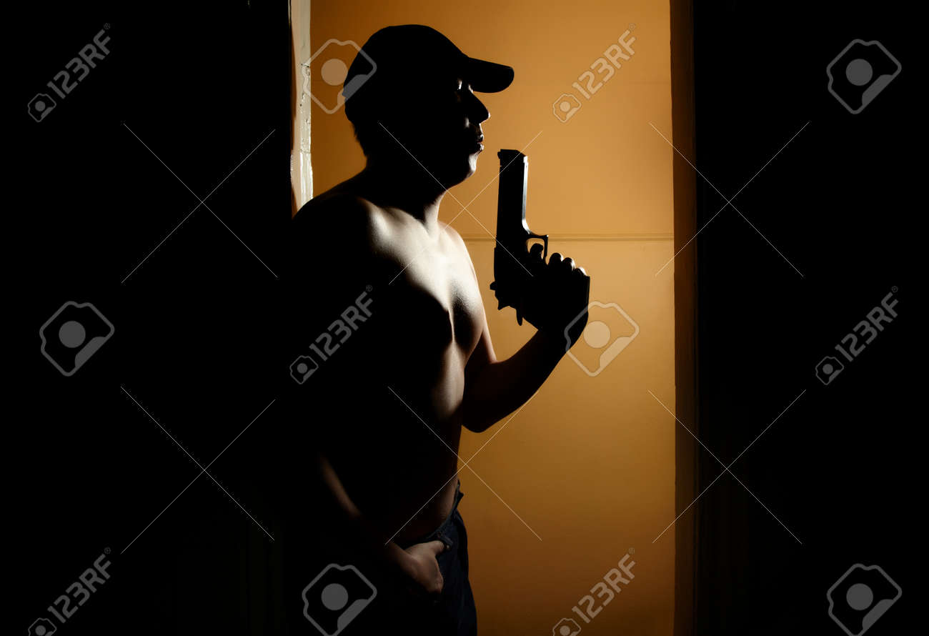 Silhouette of the muscular man with gun in the dark interior Stock Photo - 14620522