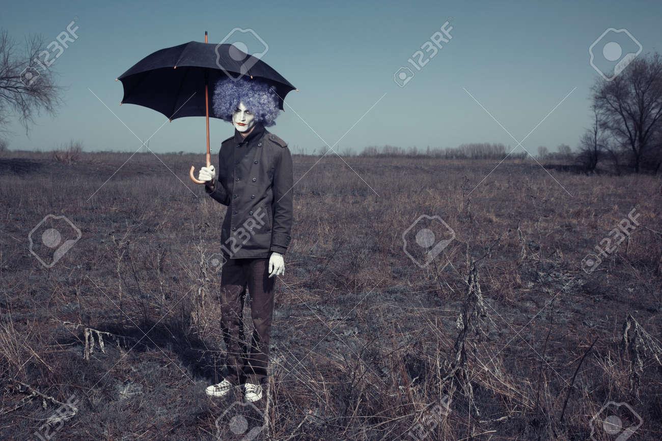 Sad clown outdoors hodling black umbrella Stock Photo - 14737277