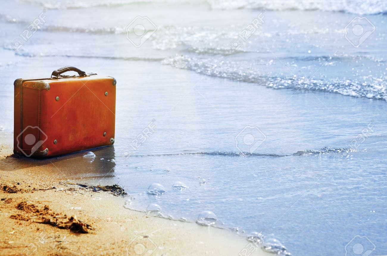 Lost orange handbag on the beach - 35179472