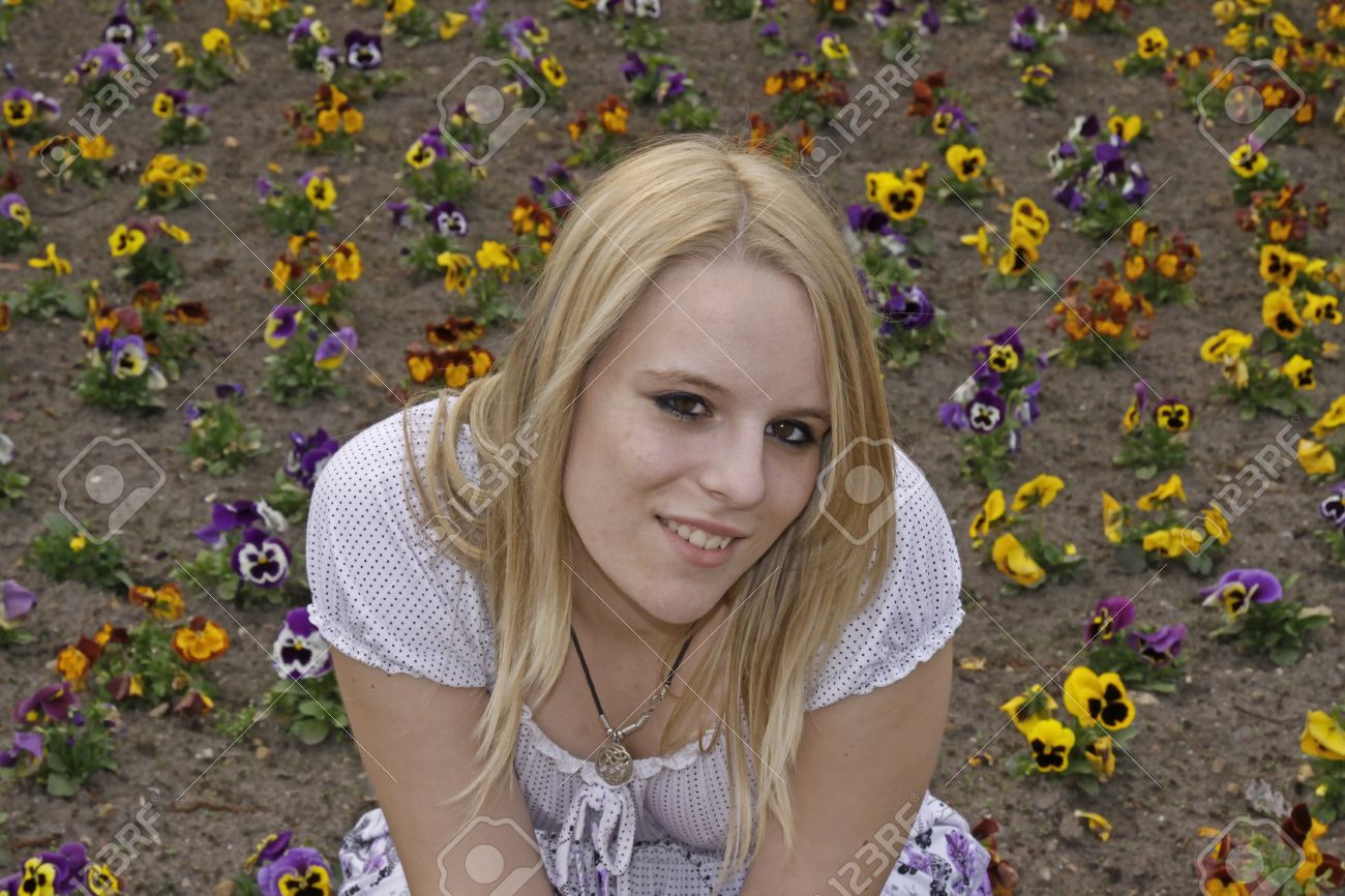 Young blond girl (17 years) in front of a flowerbed, Germany, Europe Stock Photo - 9443310