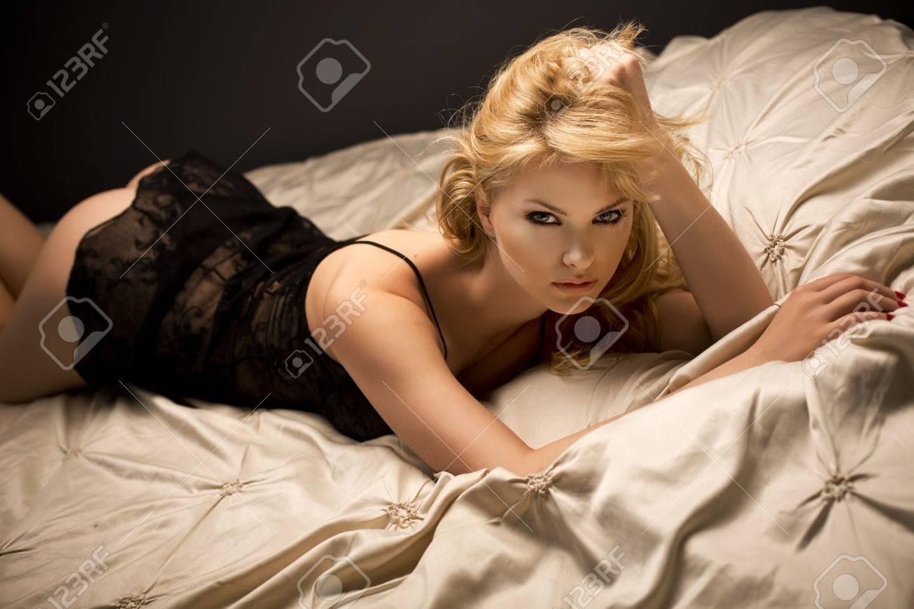 022742373596 Foto de archivo - Sexy hermosa mujer rubia acostado en la cama en ropa  interior negro sensual, mirando a la cámara
