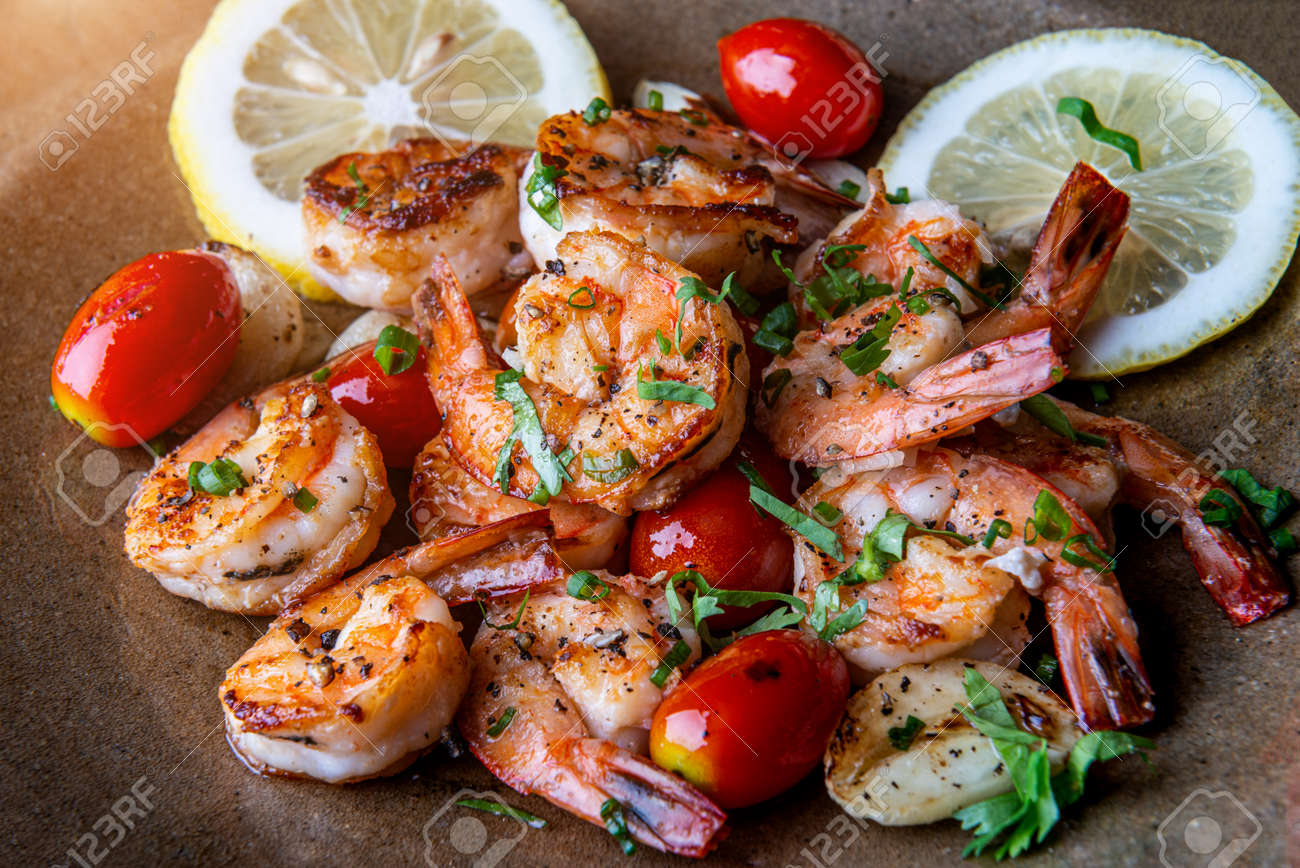 Grilled spicey shrimps with seasoning and vegetables. - 164058626