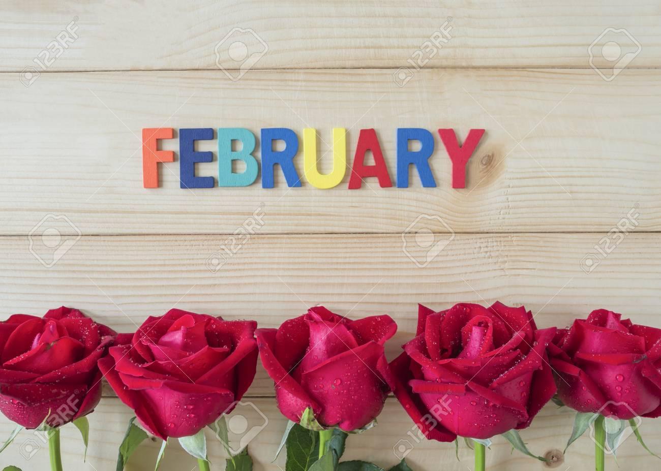 Fleur Rose Rouge Et Mot Fevrier Sur Fond De Bois Concept D Amour