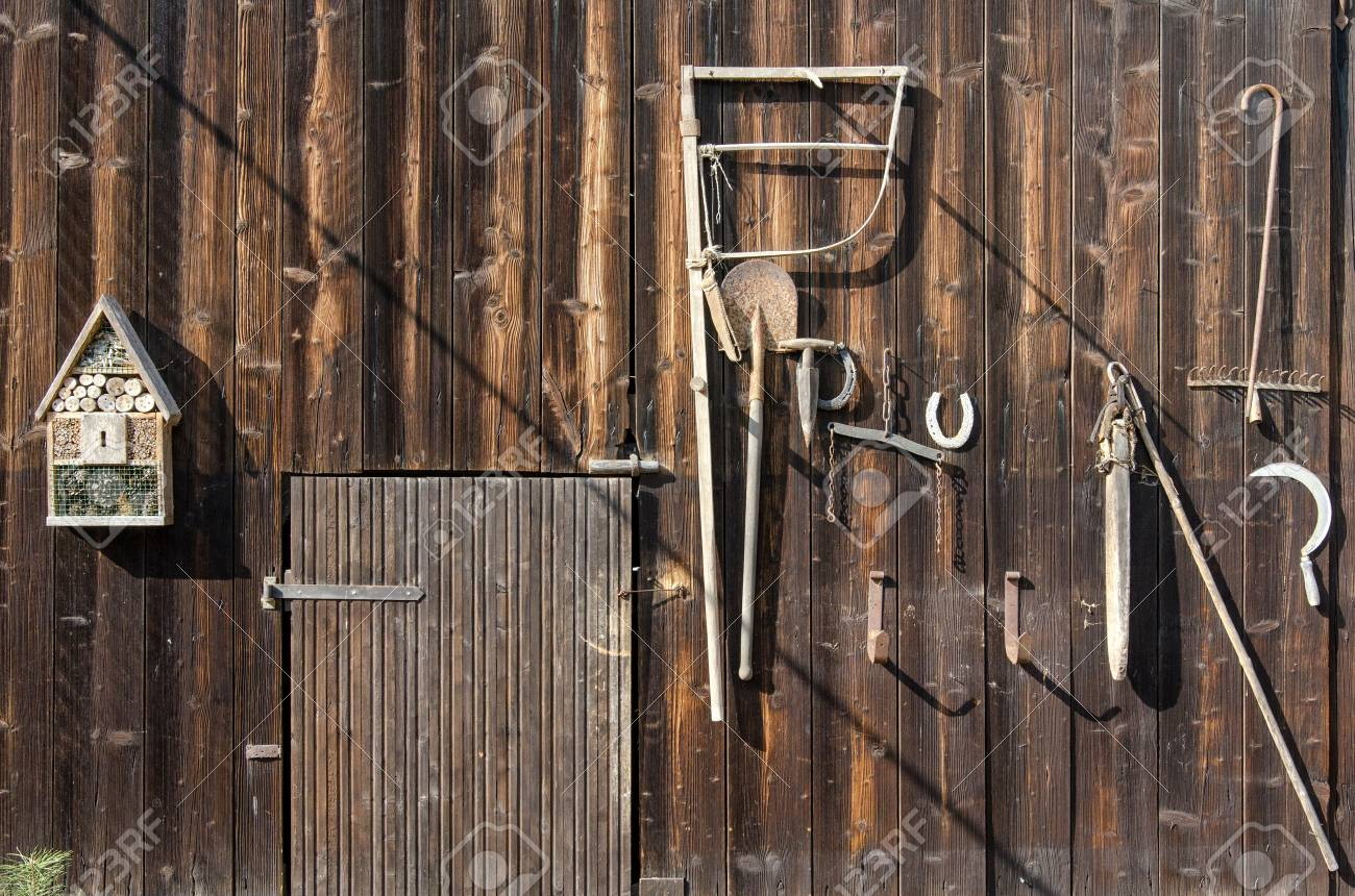 Old Rural Tools Hanging On A Wooden Barn Door As Decoration