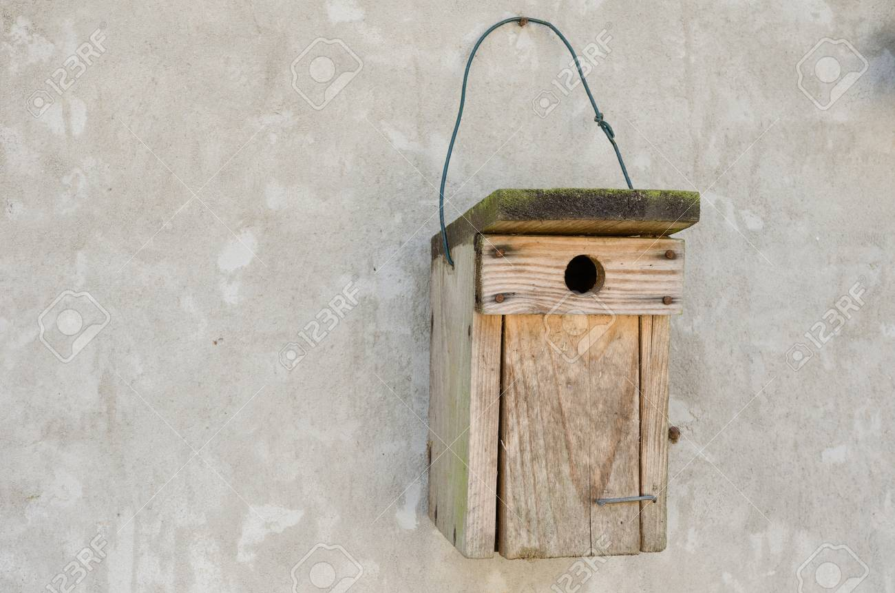 A Wooden Bird House Hanging On A Cement Wall Stock Photo Picture