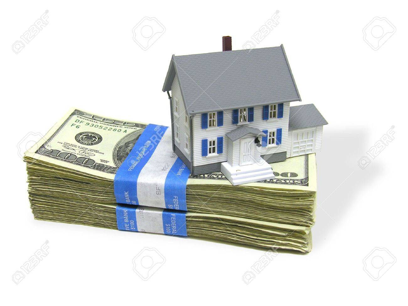 A home on a stack of cash, signifying home buying Stock Photo - 408941