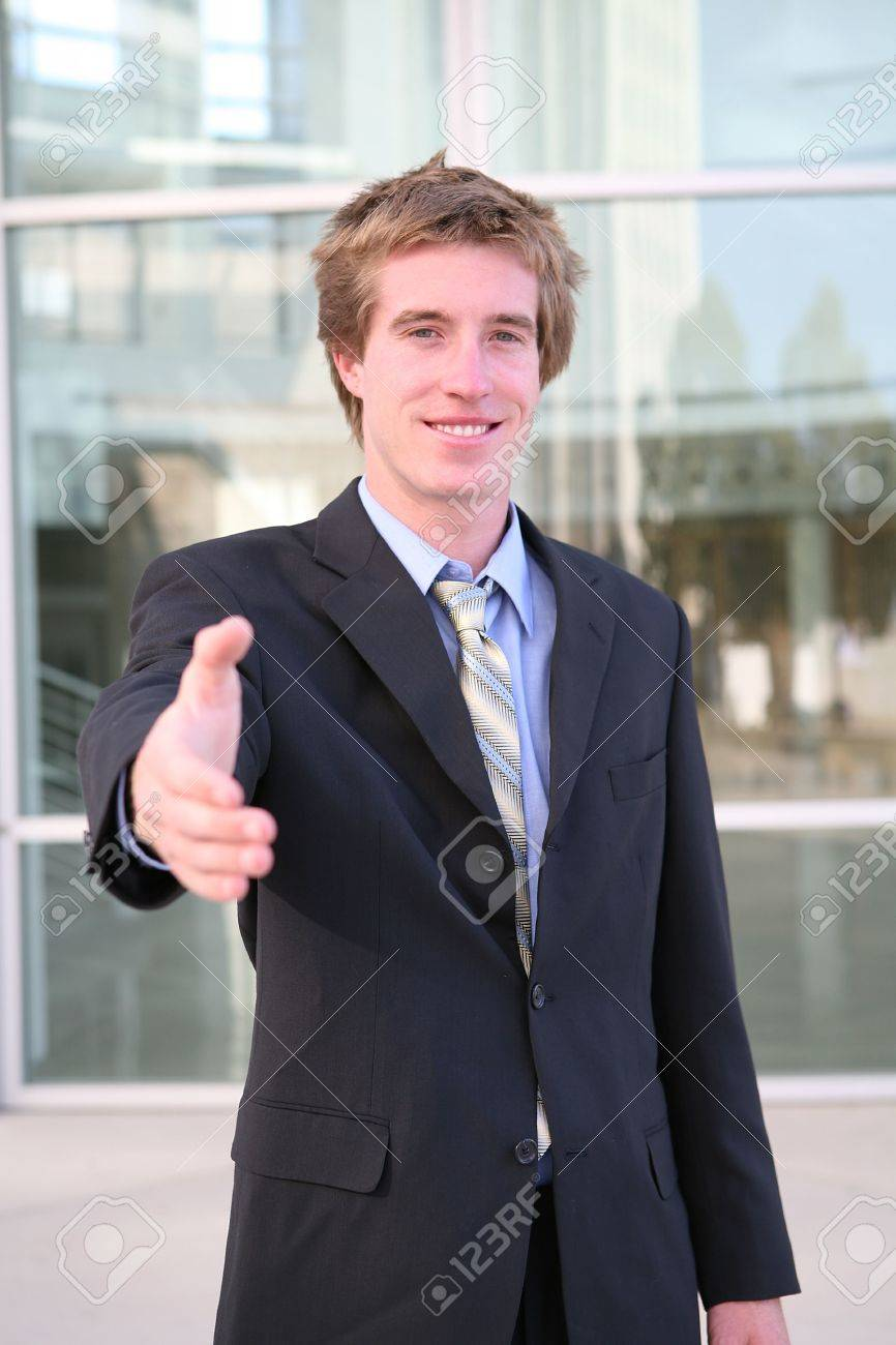 A business man offering a handshake outisde a office building Stock Photo - 603448