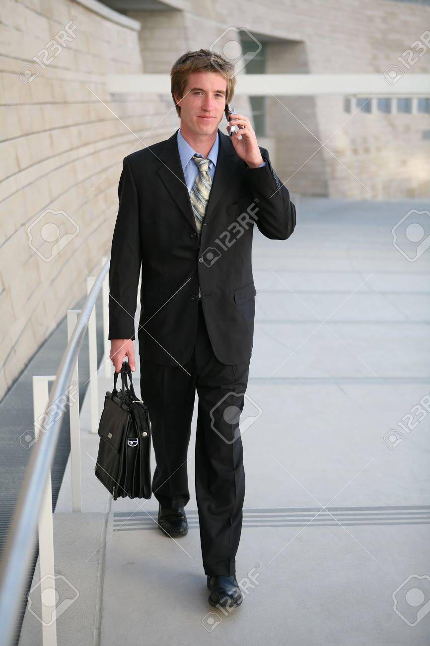 a business man walking to work talking on the phone stock photo a business man walking to work talking on the phone stock photo 603439