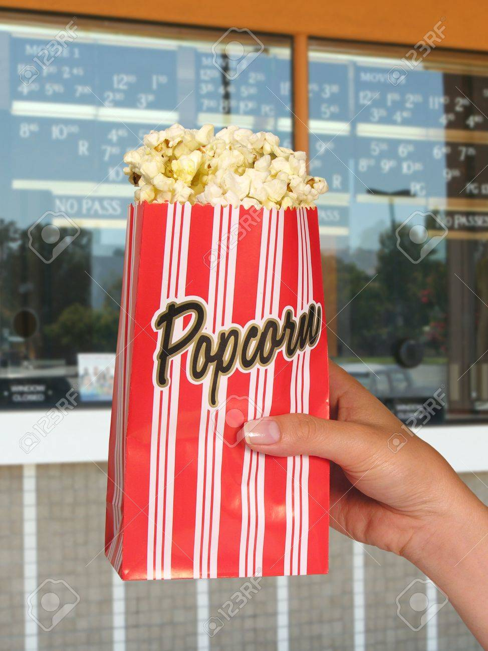 A woman holding a carton of popcorn at the movies Stock Photo - 603395