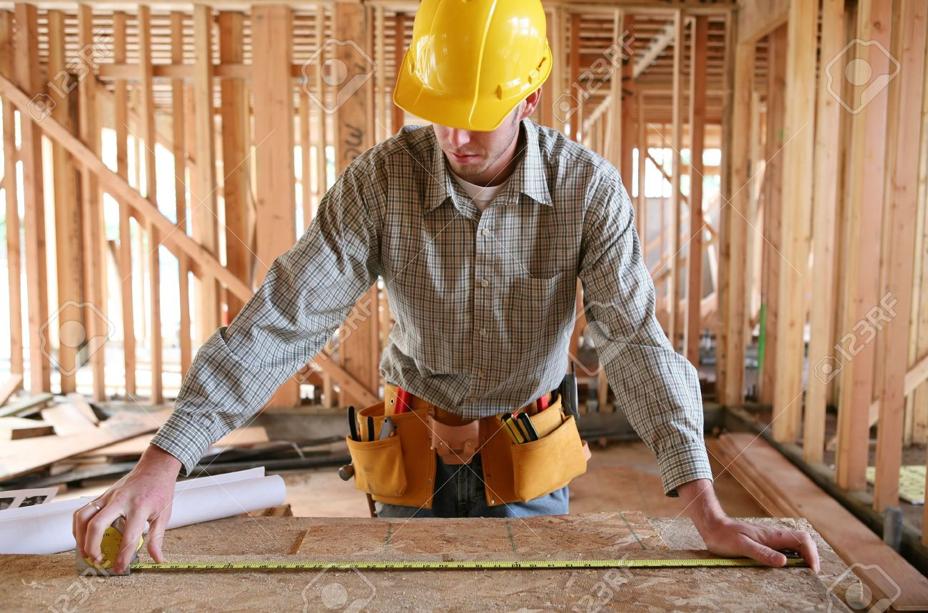 Building A Home a man working building a home and measuring some wood stock photo