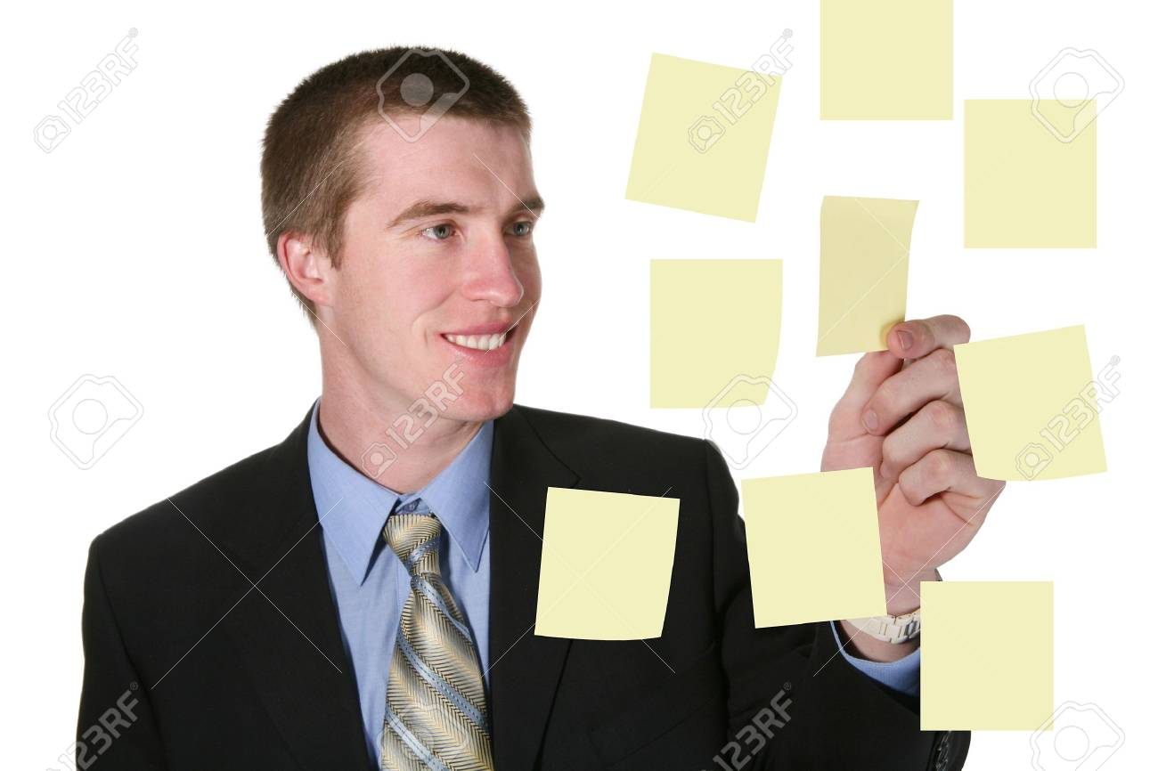 A handsome business man pulling a post-it note off the board Stock Photo - 890532