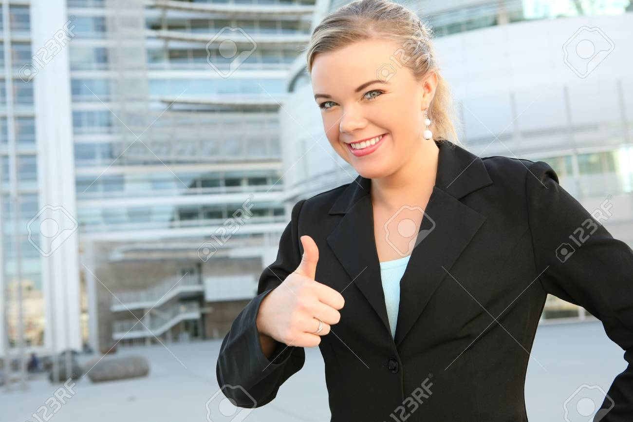 A pretty blonde business woman with her thumbs up outside office building Stock Photo - 3110527