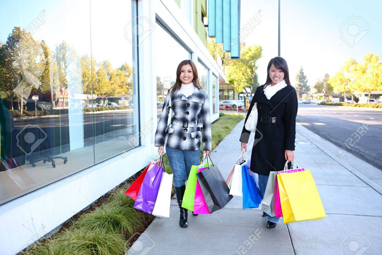 Pretty women shopping with colorful bags walking to the next store Stock Photo - 6024640