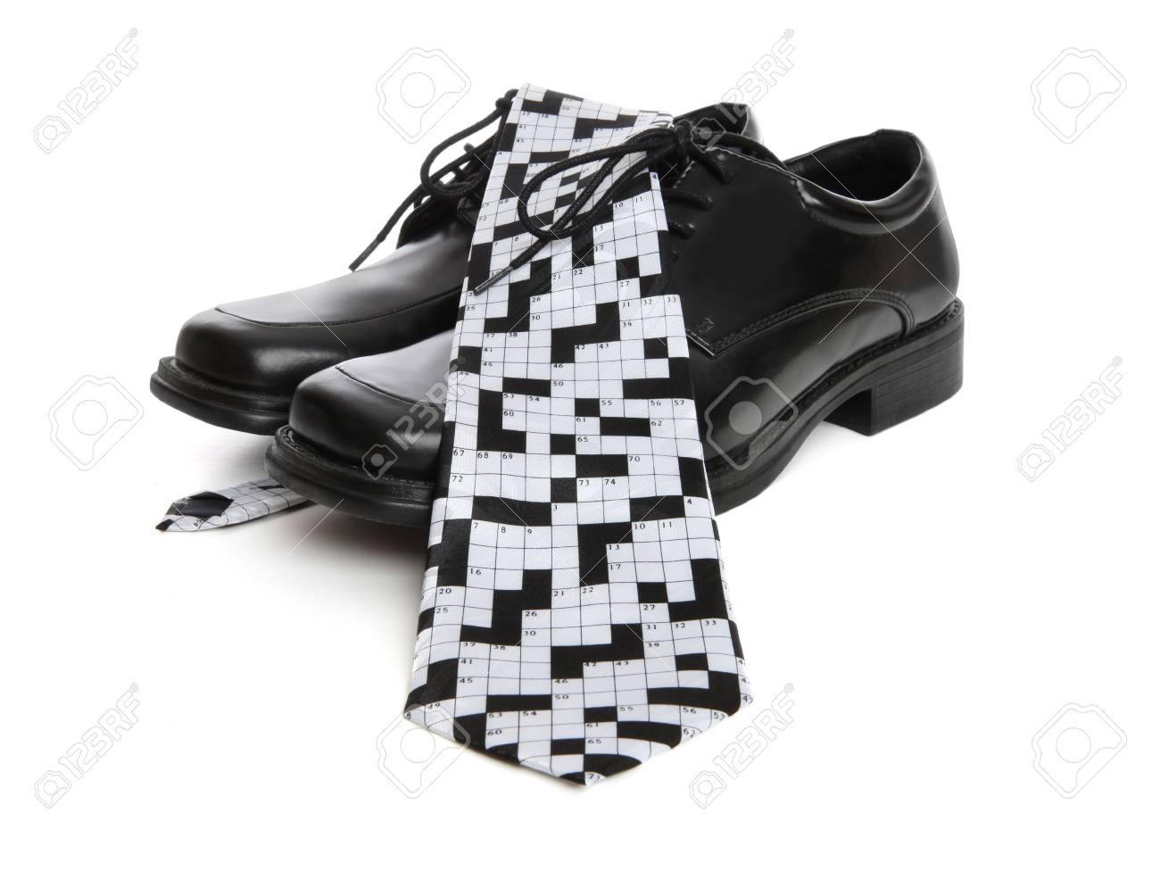 A Business Mans Shoes And A Crosswork Puzzle Tie Over White Stock