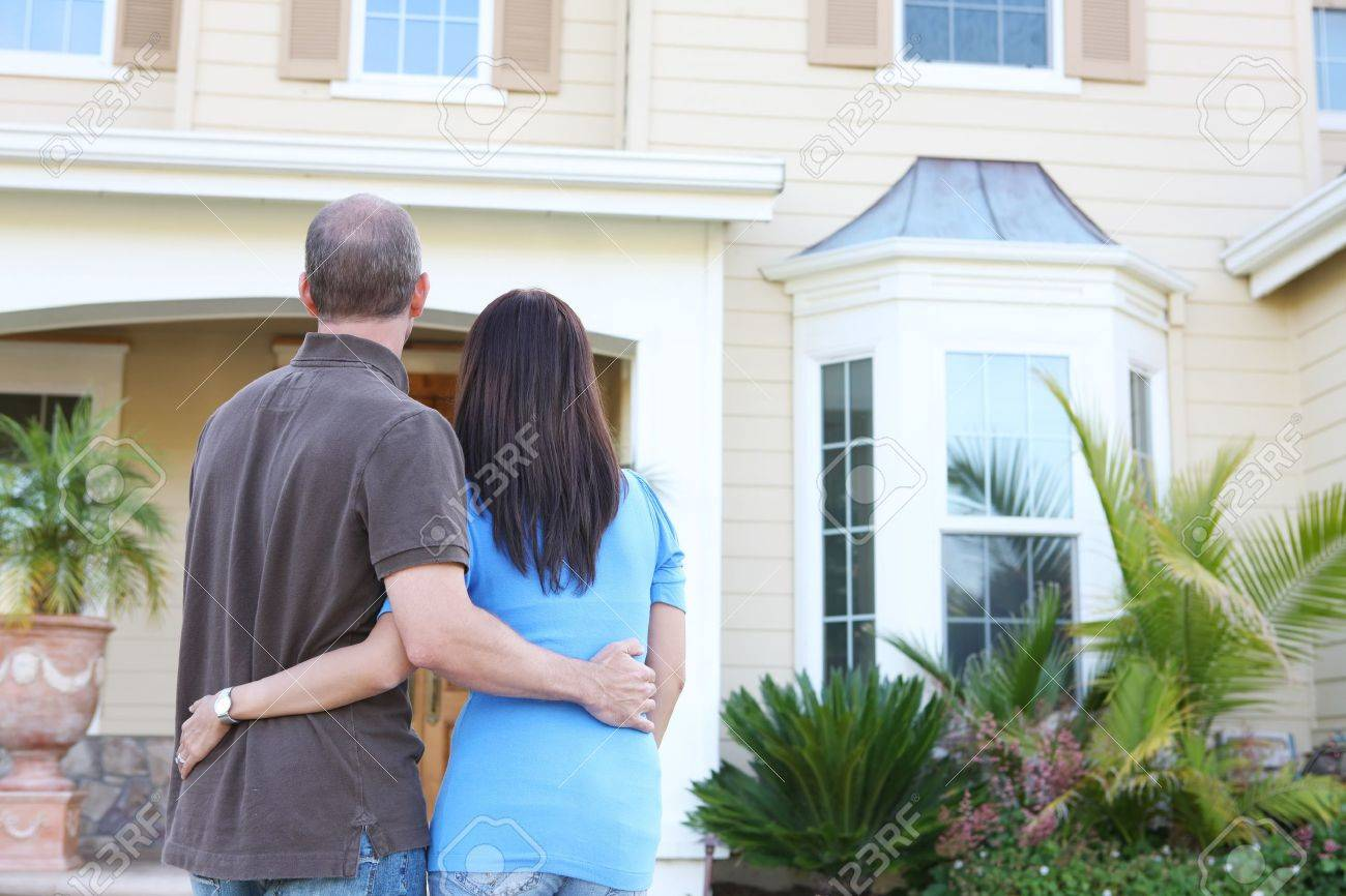 An attractive happy newlywed couple in front of their home in love Stock Photo - 10184106