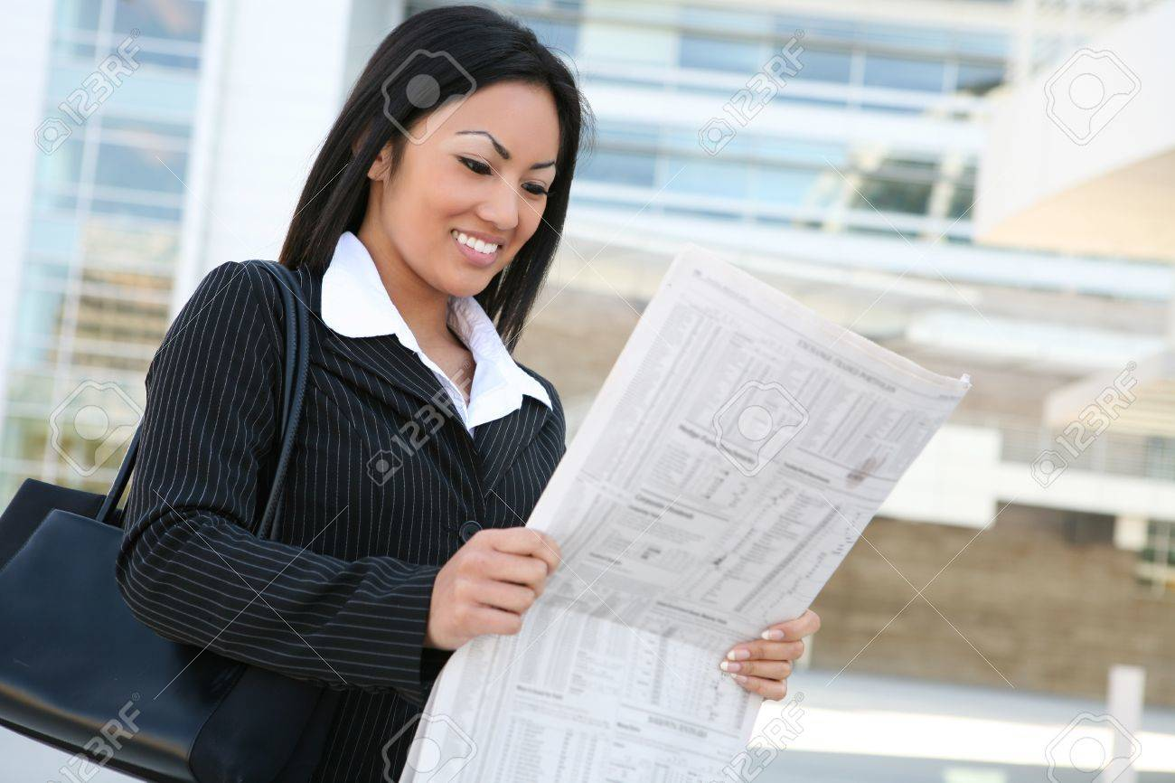 A pretty asian business woman reading the newspaper outside company Stock Photo - 10830176