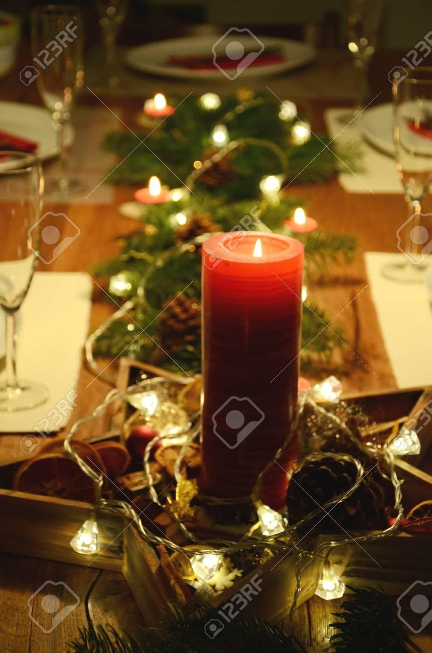 Deco De Table Bougie décoration de table de noël avec bougie rouge et de brindilles de sapin  couché sur la table avec des lumières de guirlande électrique sur