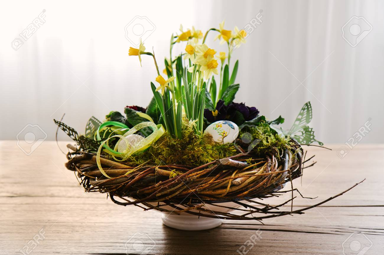 Easter Table Centerpiece Decoration With Daffodils And Eggs Arranged In A Rustic Wreath Made Of