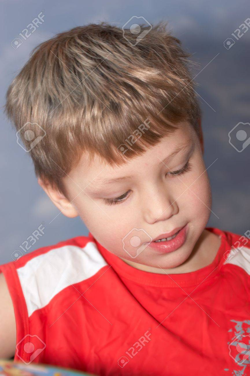 Young boy reading the book and thinking about it Stock Photo - 2305442