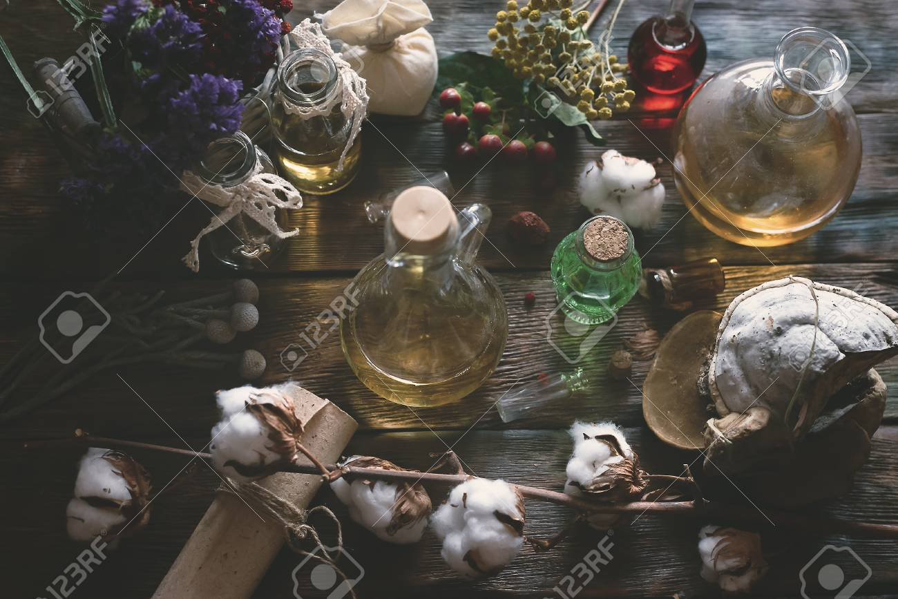 Herbal medicine essential oil and various dry herb on a table
