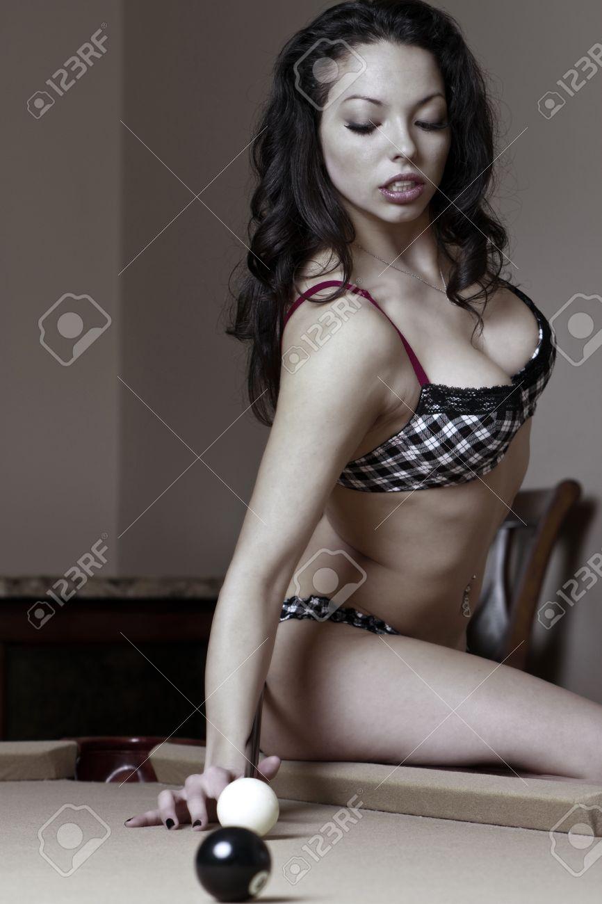 Sexy girl in bikini taking a difficult pool shot. Stock Photo - 12042793