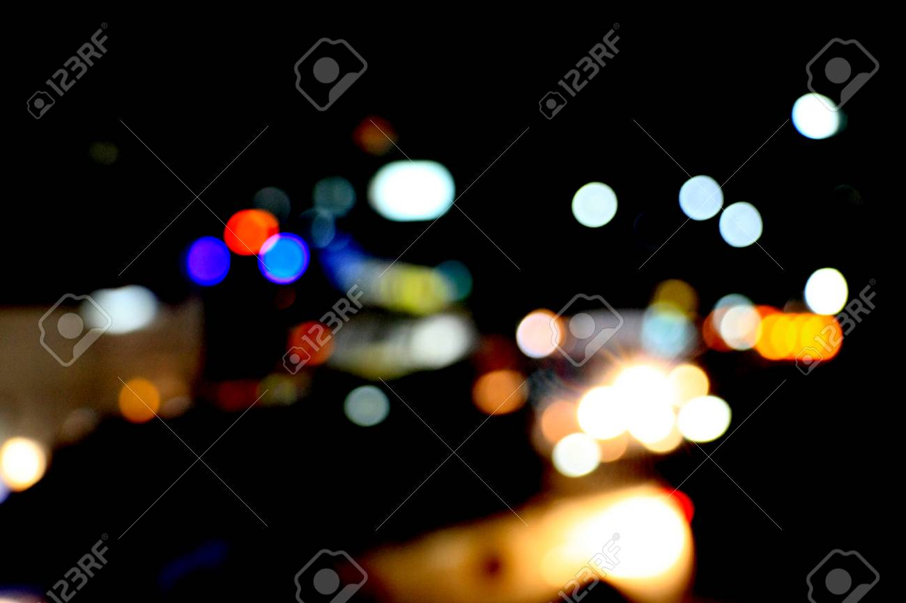 Real Light blur bokeh in dark background from lens out focus. Red blue green yellow light neon at bar.it look like circle light many color blur at night on street in big city in celebration time - 100733830
