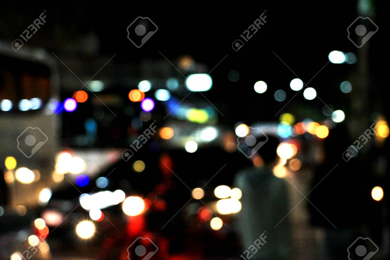 Real Light blur bokeh in dark background from lens out focus. Red blue green yellow light neon at bar.it look like circle light many color blur at night on street in big city in celebration time - 100740164