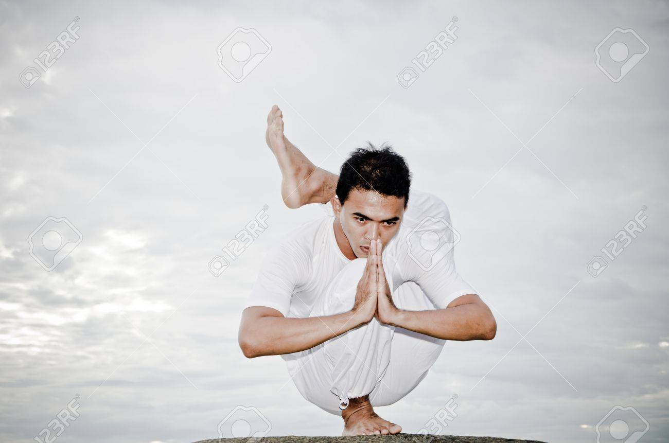 young Asian man doing yoga on the beach - 14264693