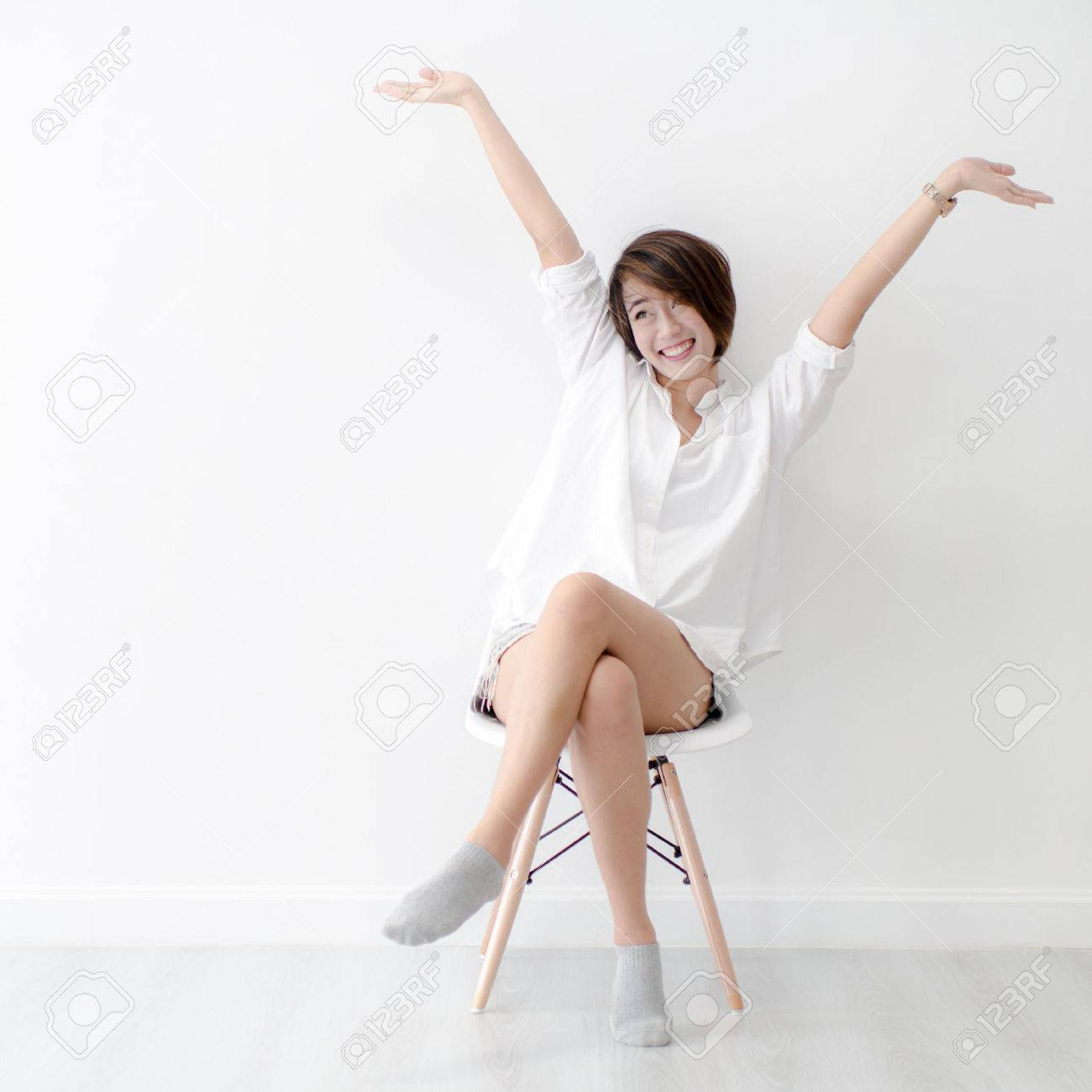 Attractive Asian girl sitting on white modern chair and relax at home. - 59147231