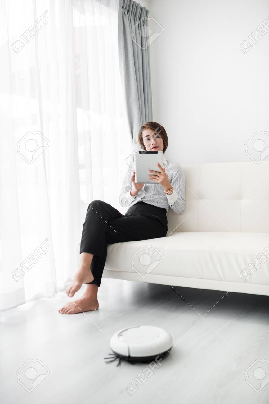 Smart businesswoman using smart phone and cleaning robot, lifestyle concept. - 95637388