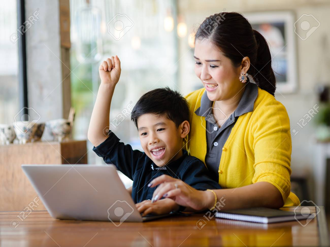 Happy Asian mother and her son raising their hands while win the online game together. - 97946616