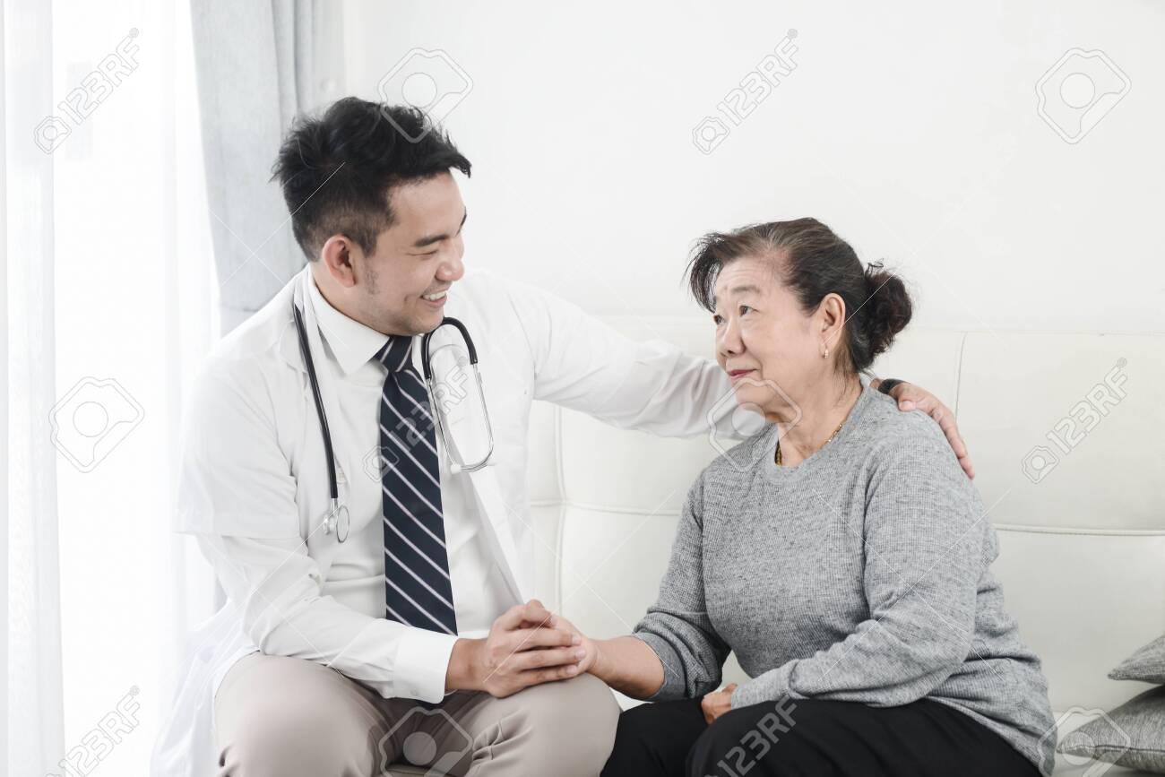Asian doctor checking up his patient old woman in office. - 129907988