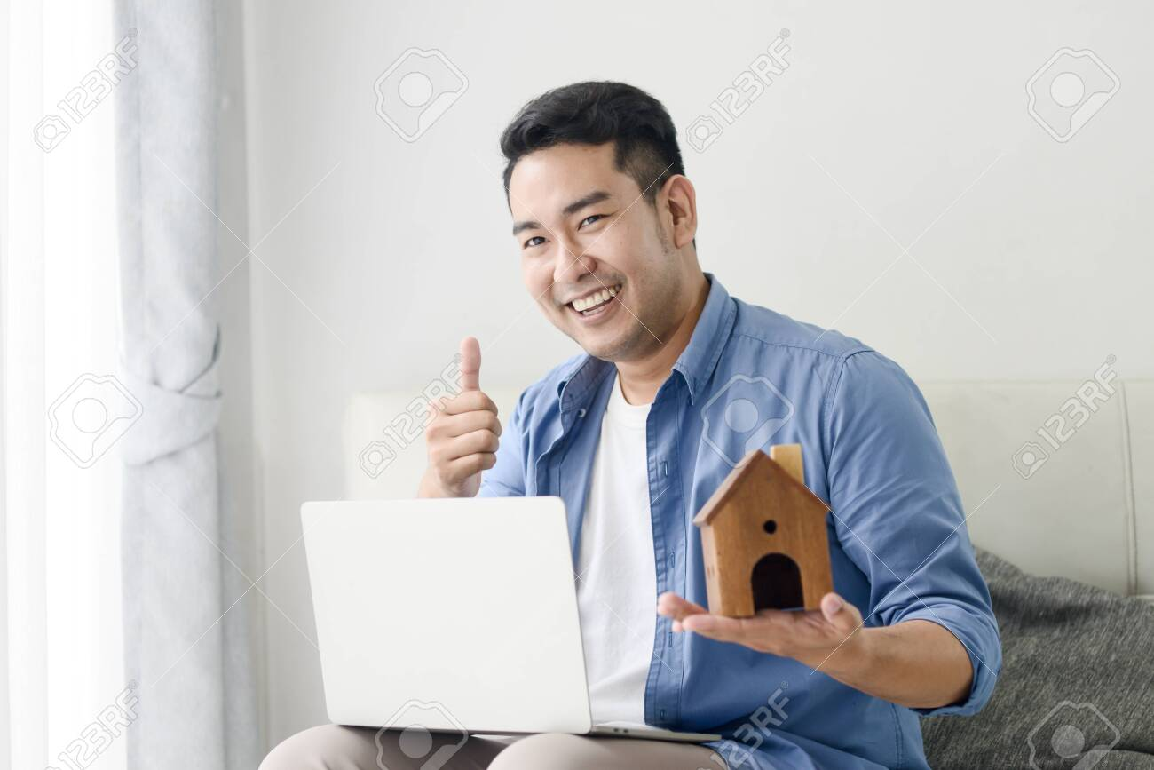 Asian man holding house in his hand and using laptop, real estate concept. - 129901049