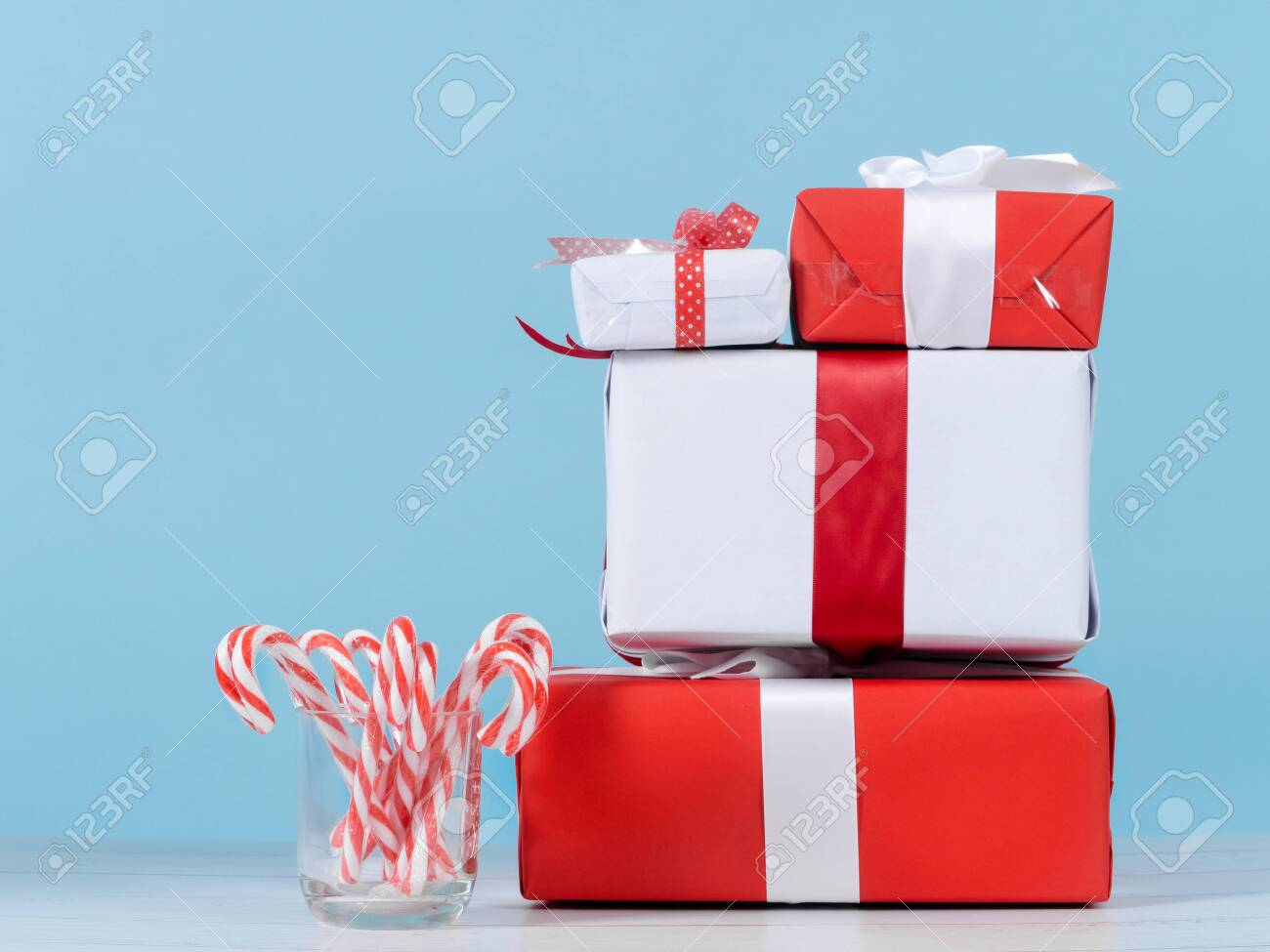 Red and white gift boxes and Christmas candy sticks on wooden table with blue wall. - 135085559