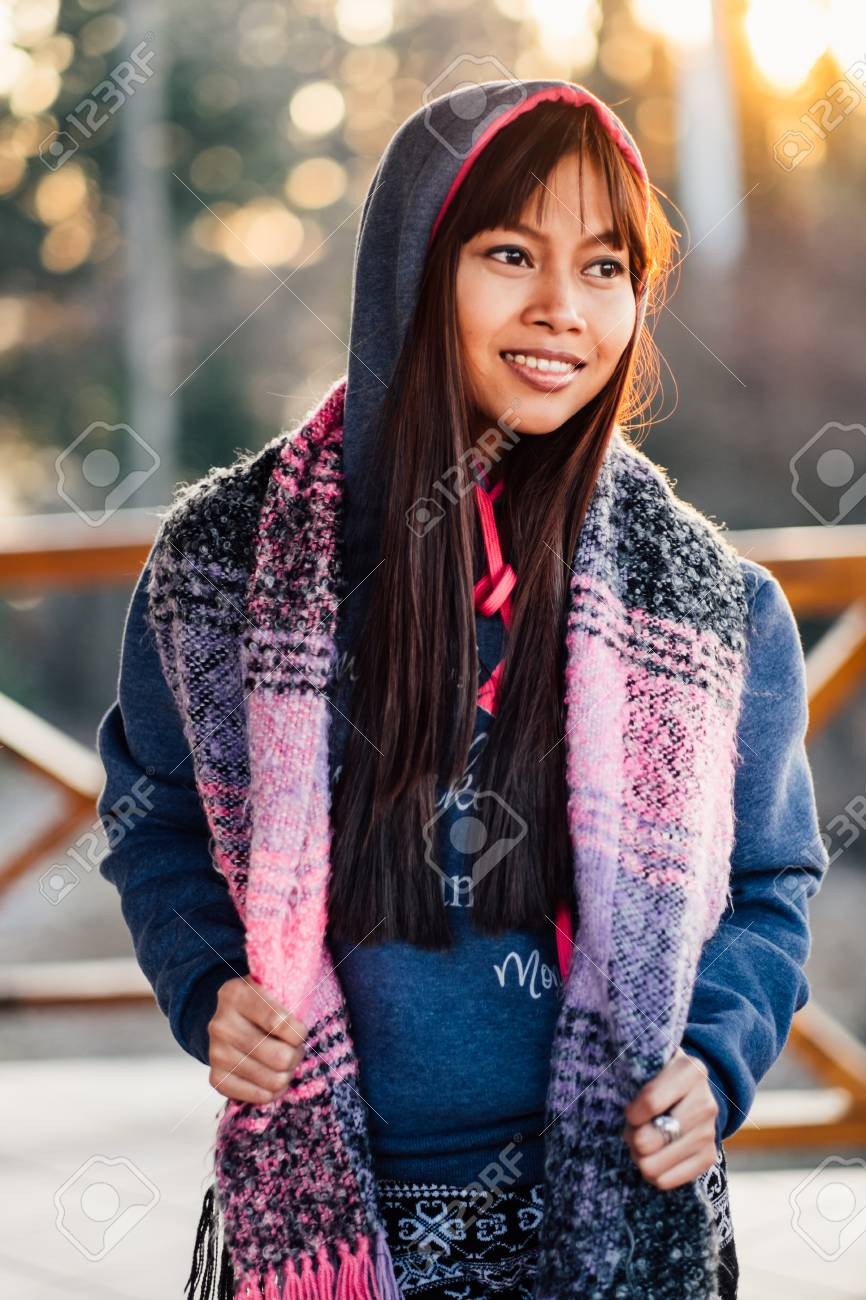 dd58d2e9ab Stock Photo - Young beautiful wman in a blue sweater with colorful scarf  during cold weather outside the balcony.