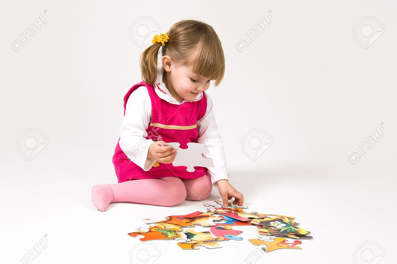 Little girl is solving puzzle on white background - 5727258
