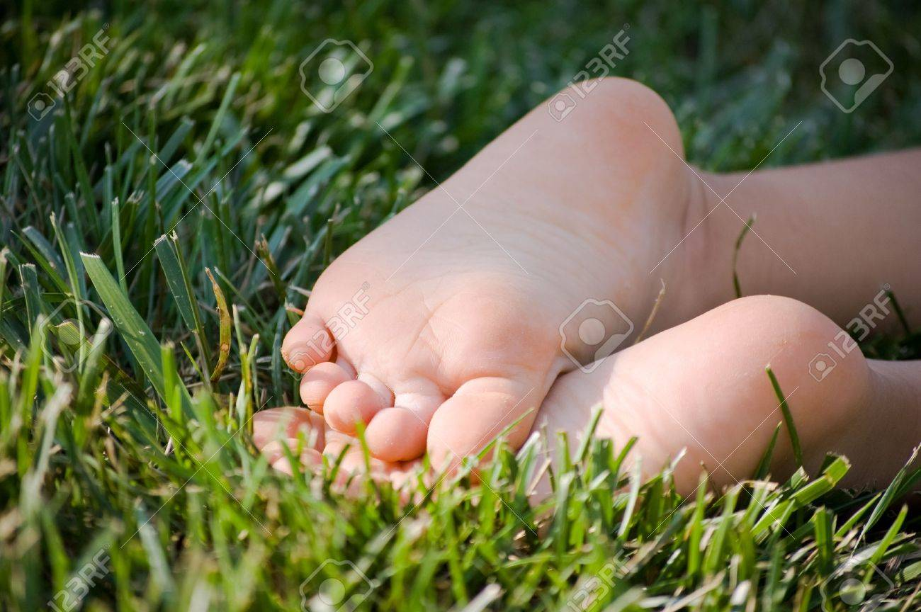 Child's bare feet in green grass Stock Photo - 5916289
