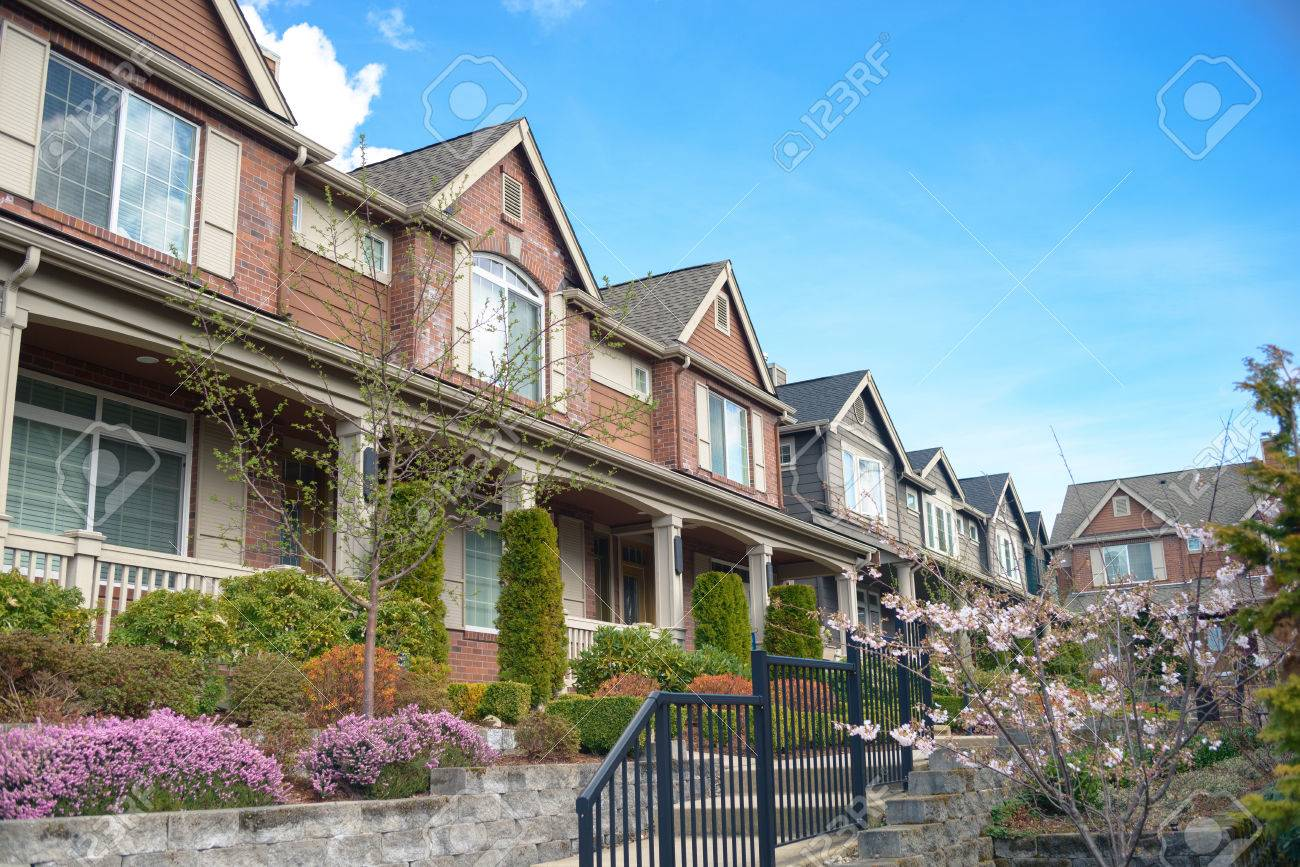 American street with townhouses with nice landscaping under blue sky - 38066893